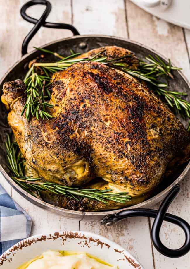 side crockpot whole chicken in serving dish with rosemary