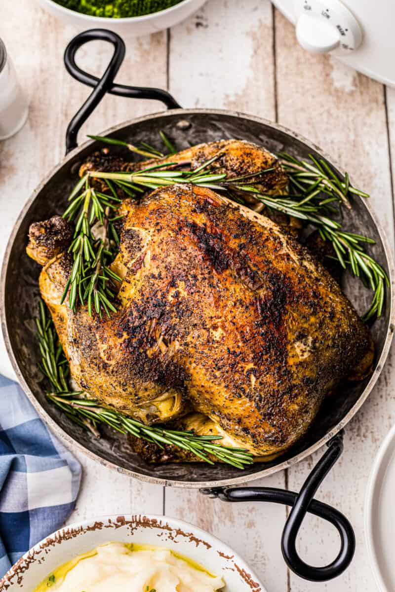 overhead crockpot whole chicken in serving dish with rosemary