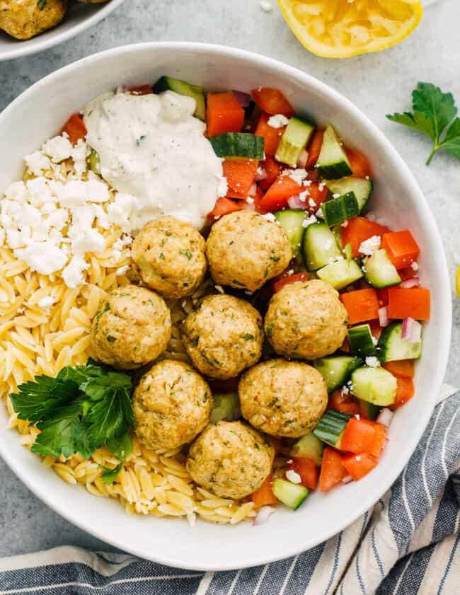 Greek chicken meatballs over veggies, rice and tzatziki sauce