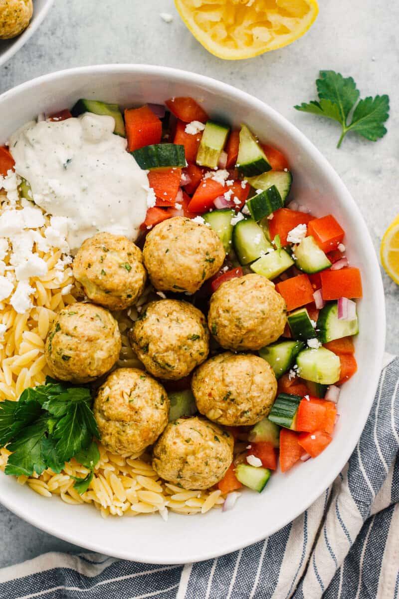 up close Greek chicken meatballs over veggies, rice and tzatziki sauce
