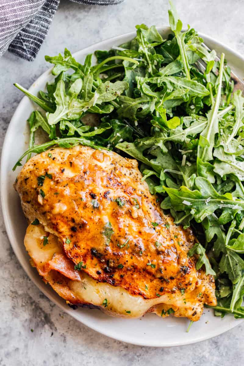 overhead ham and cheese stuffed chicken with salad on white plate