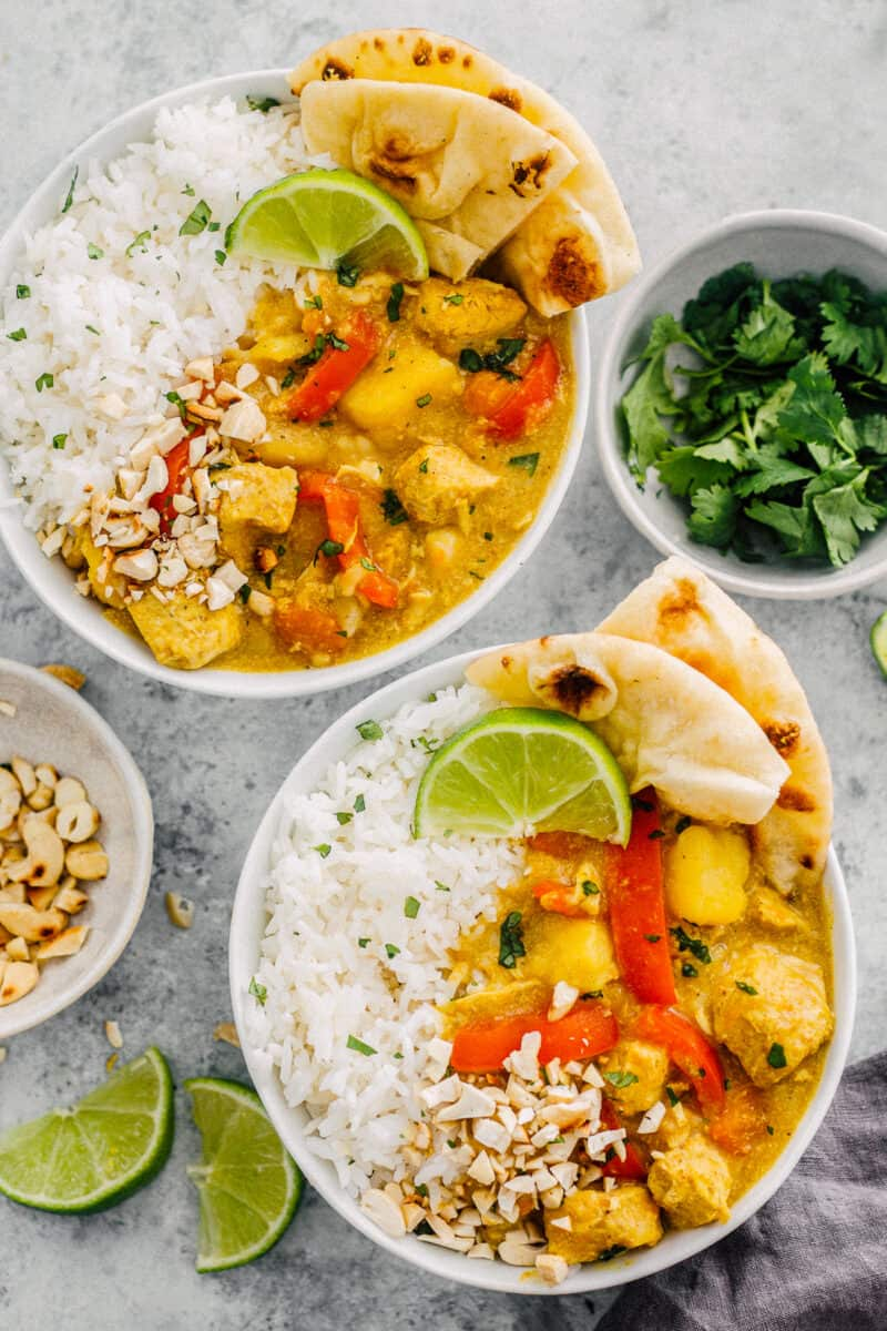 two bowls of instant pot chicken curry over white rice with naan