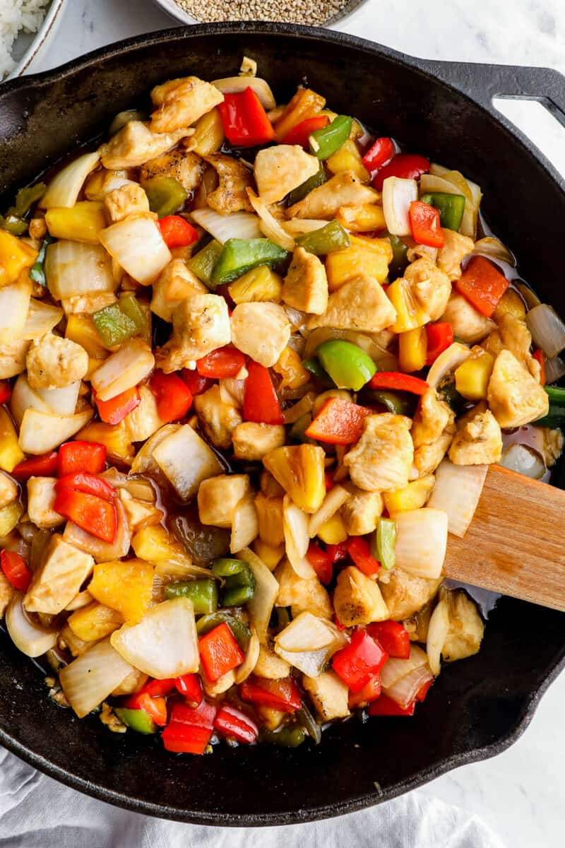 sweet and sour chicken in skillet with wooden spoon