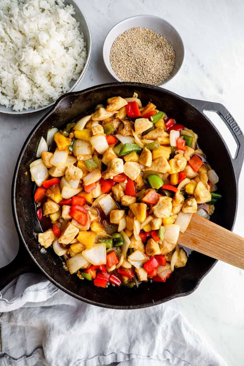 skillet with sweet and sour chicken next to write rice