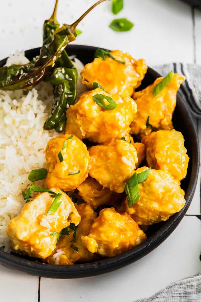air fryer orange chicken with rice on black plate