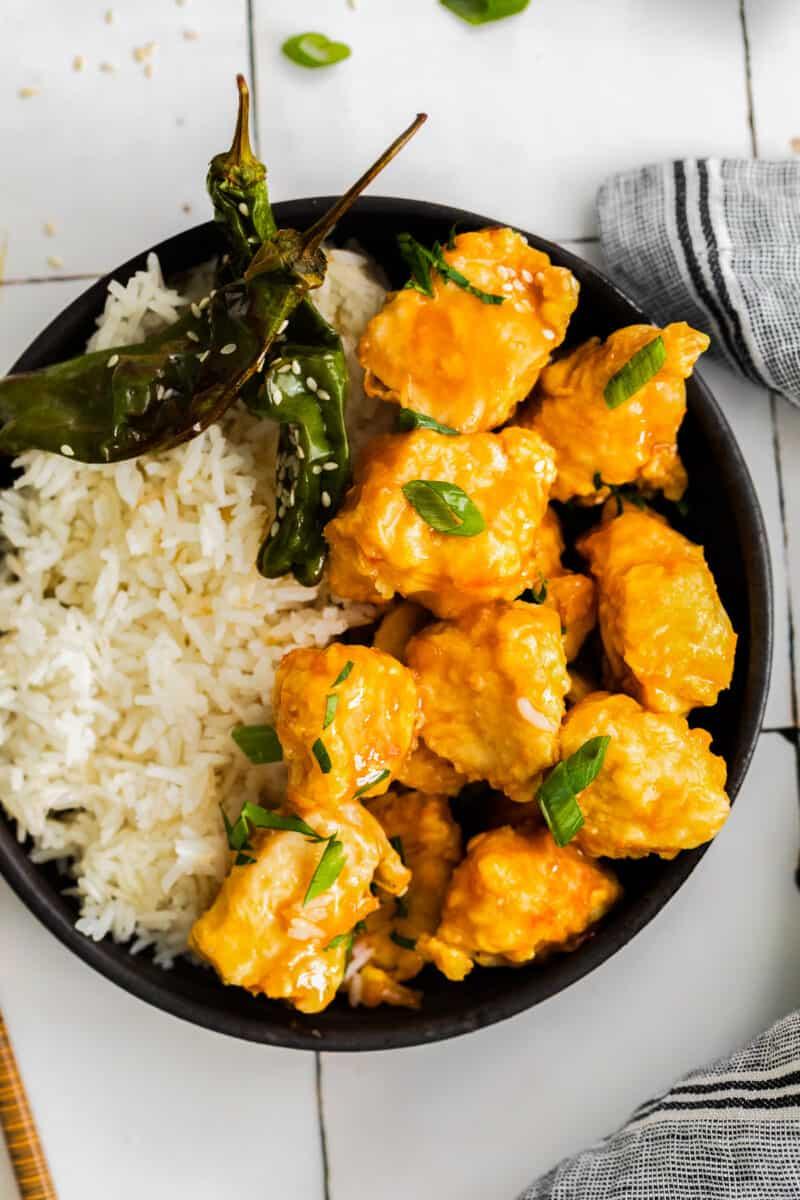 overhead air fryer orange chicken with rice on black plate