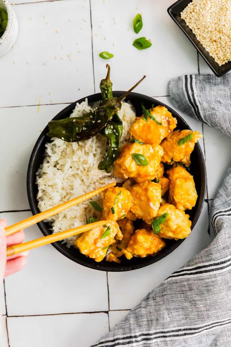 eating air fryer orange chicken with chopsticks