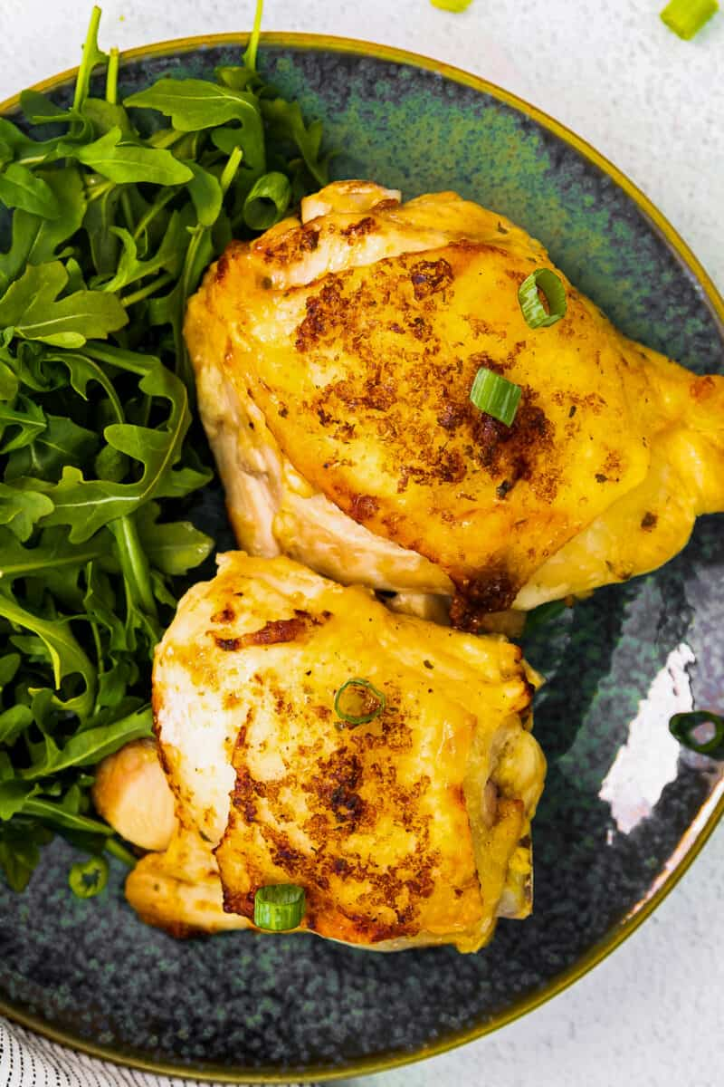 up close air fryer ranch chicken thighs on blue plate with salad