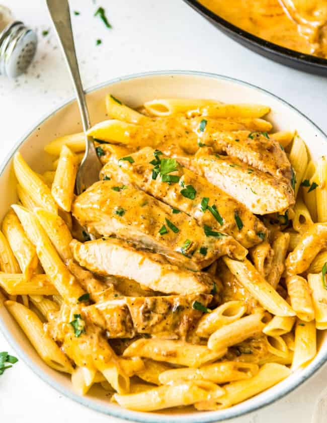 sliced chicken lazone over pasta in white bowl