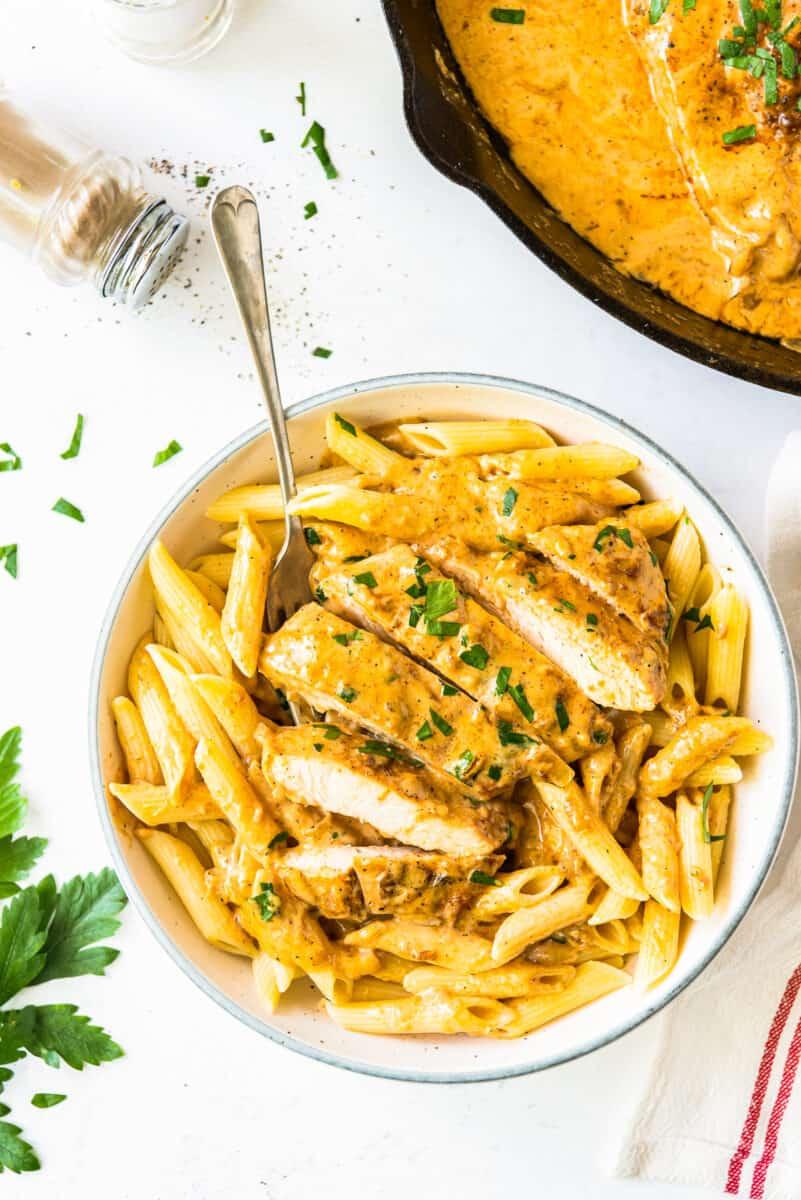 overhead chicken lazone over pasta in white bowl