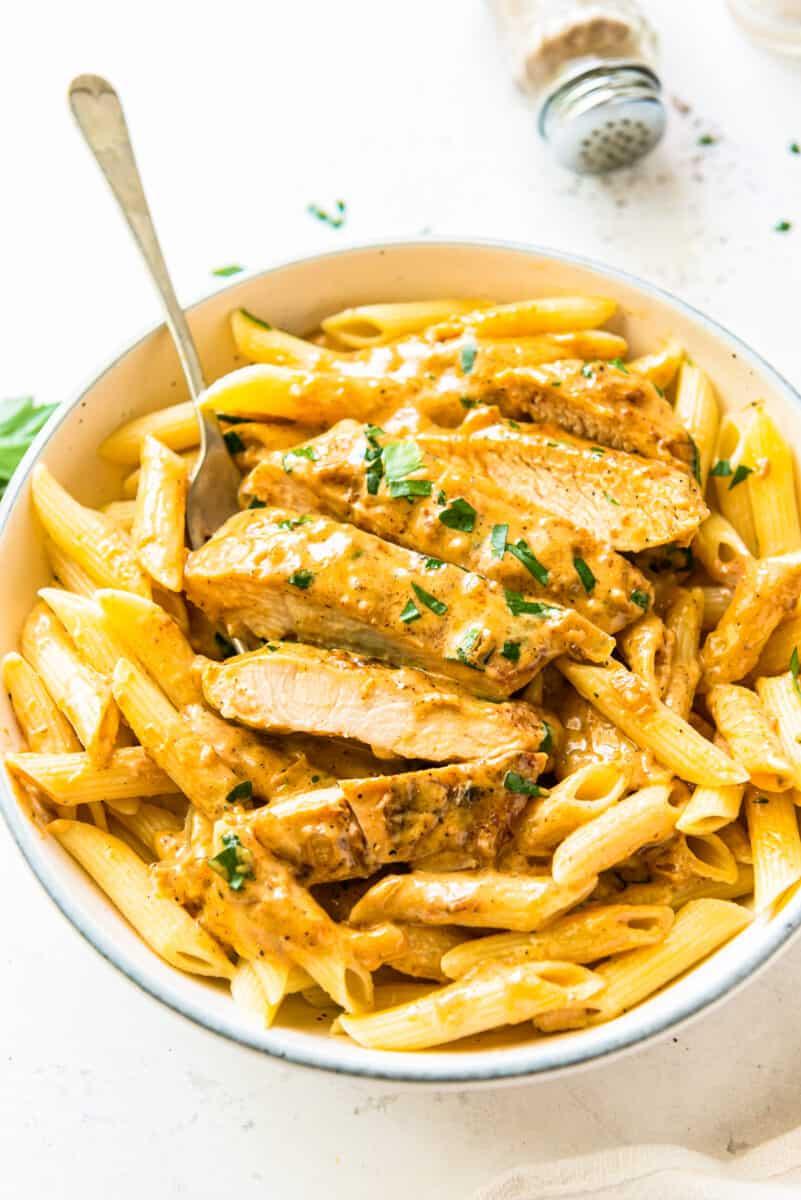 overhead sliced chicken lazone over pasta in white bowl