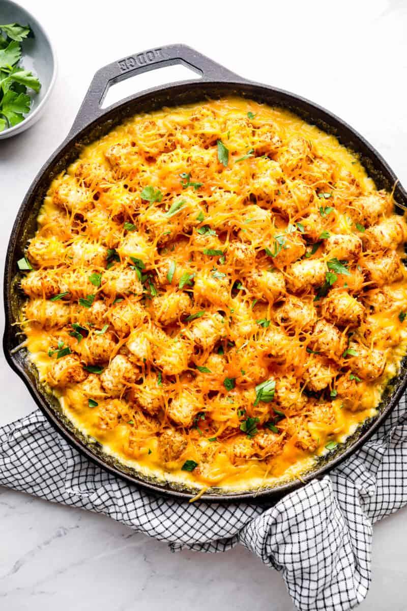 overhead cheesy tater tot chicken casserole in cast iron skillet