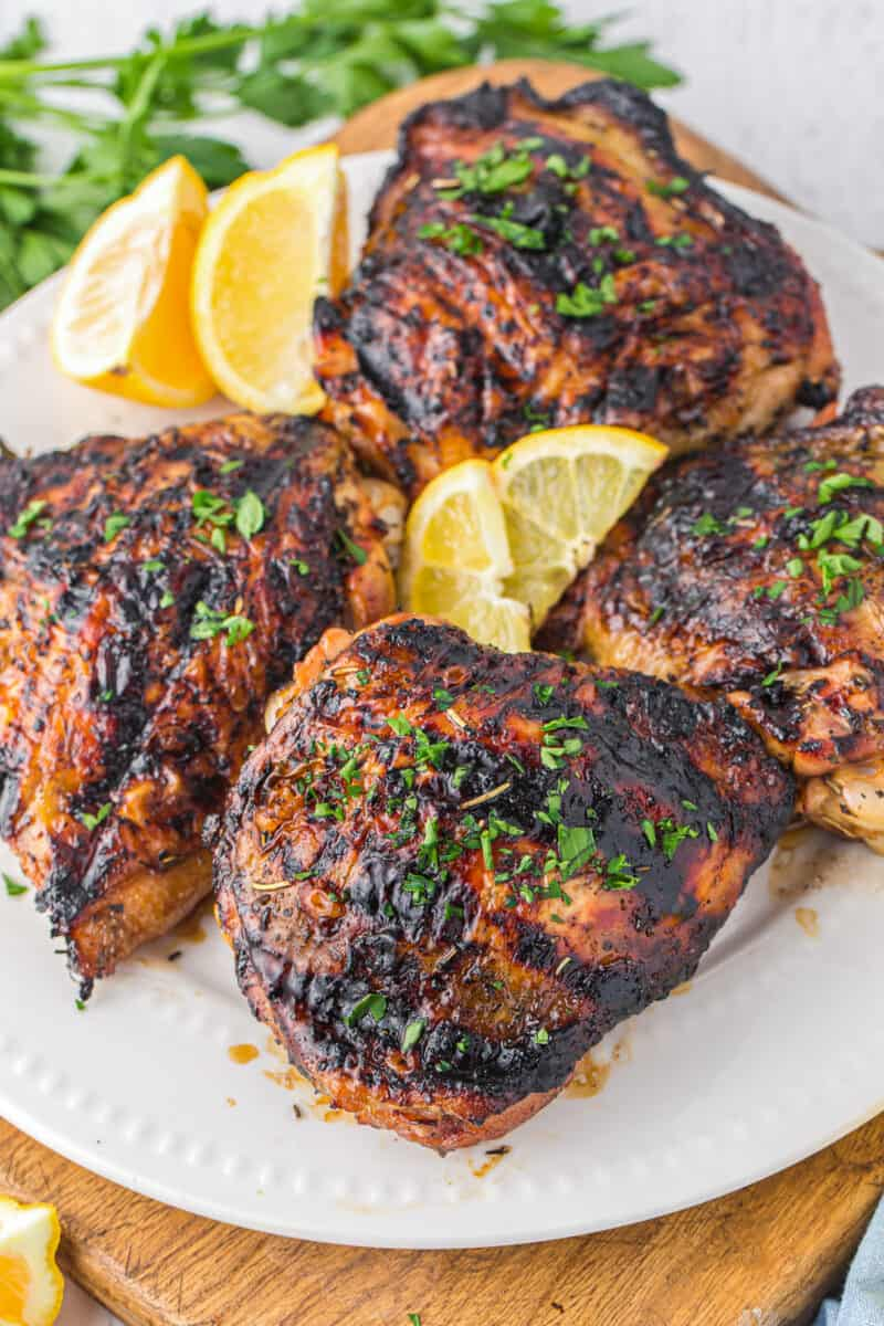 4 marinated grilled chicken thighs on white platter