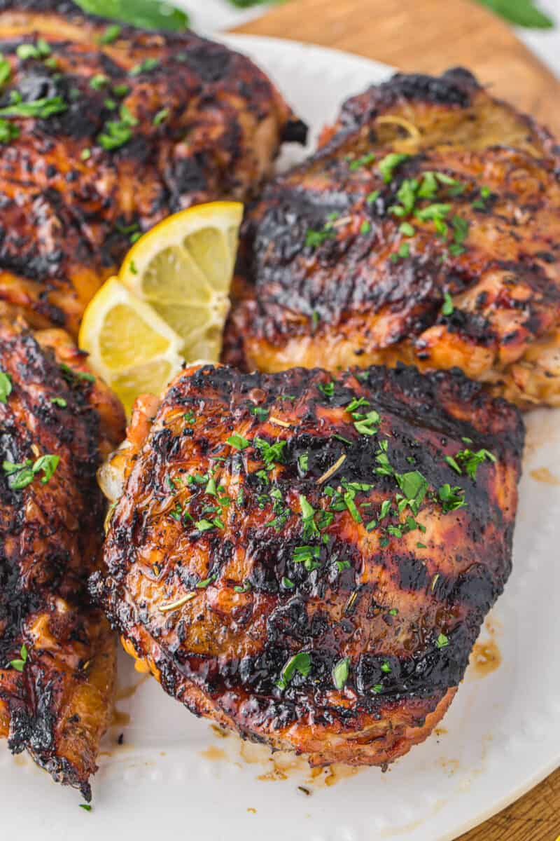 up close 4 marinated grilled chicken thighs on white platter