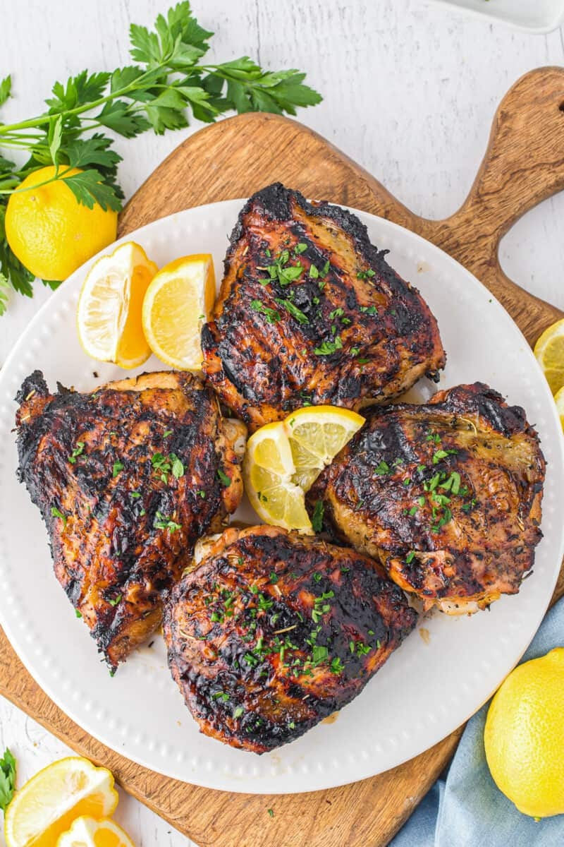 overhead 4 marinated grilled chicken thighs on white platter