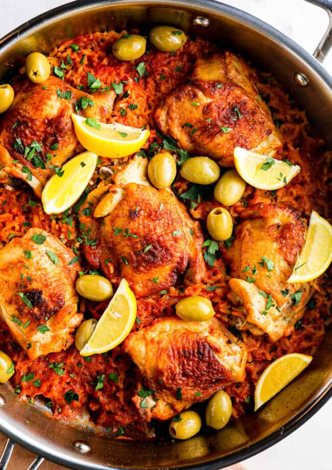 up close Spanish chicken and rice with lemon slices and olives